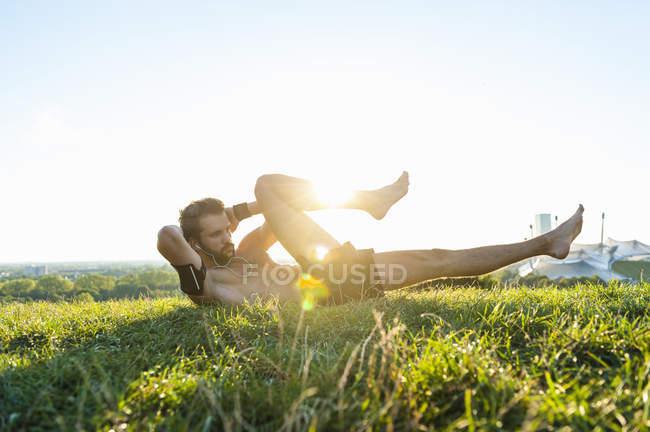 Активный человек, делать приседания на лугу — стоковое фото