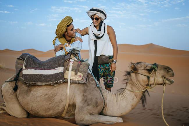 Berber Mann mit Frau Tourist mit einem Kamel in der Wüste — Stockfoto