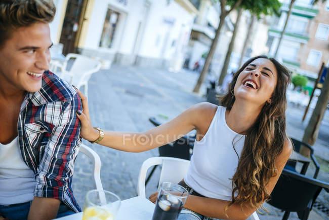 Jovem casal se divertindo no café calçada — Fotografia de Stock
