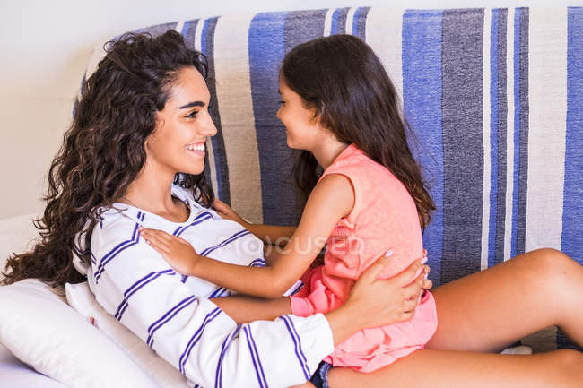 Adolescente sorridente e la sua sorellina si fronteggiano — Foto stock