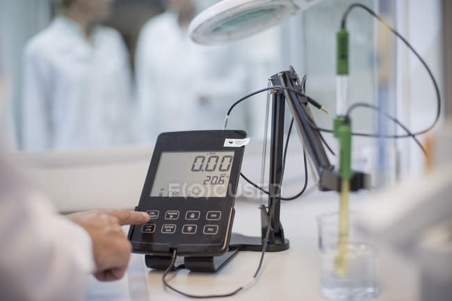 Cropped image of scientist in lab checking measurements — Stock Photo