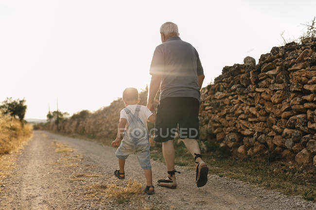 Little boy and great-grandfather walking on dirt track at backlit — Stock Photo
