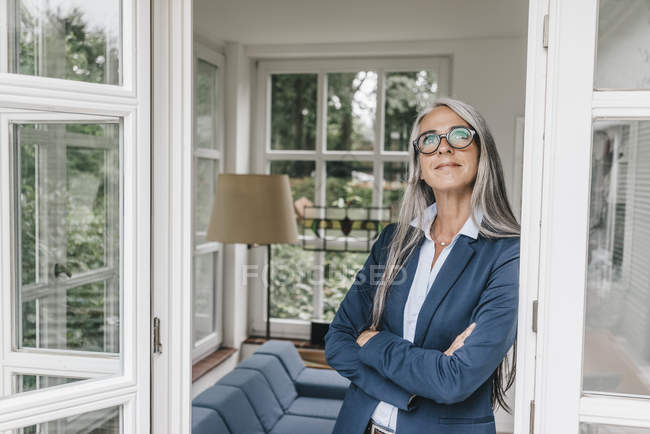 Businesswoman leaning against door case — Stock Photo