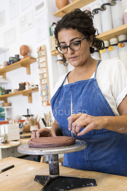 Woman working with clay in a ceramics workshop — Stock Photo
