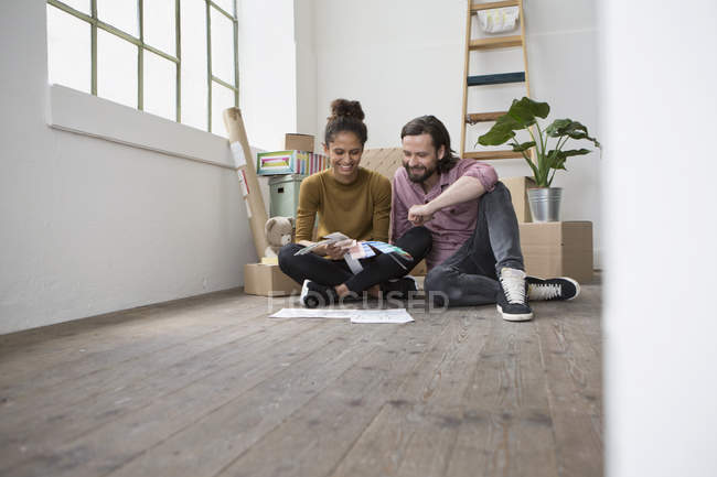 Couple sitting on floor of new flat choosing from color samples — Stock Photo