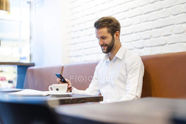 Lächelnde Geschäftsmann mit Handy im café — Stockfoto