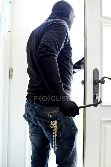 Burglar with pearl necklace in pocket leaving house at daytime — Stock Photo