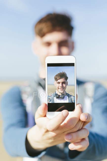 Mann zeigt Display des Smartphones — Stockfoto