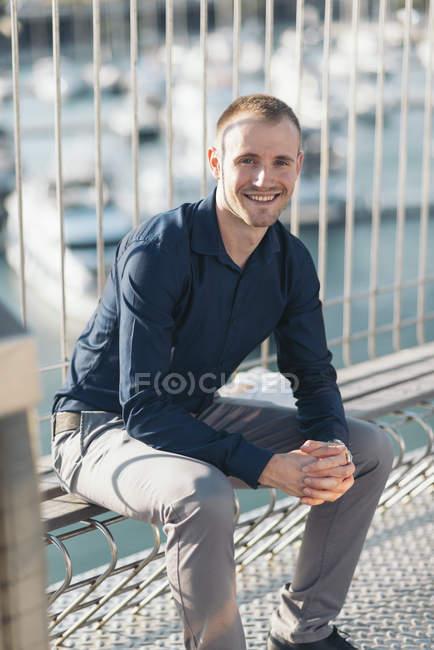 Empresário sorridente sentado em frente ao porto à luz do sol — Fotografia de Stock