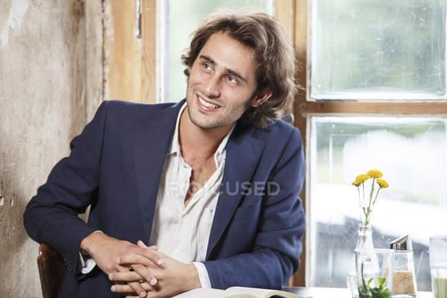 Портрет улыбающегося молодого человека, сидящего в кафе — стоковое фото