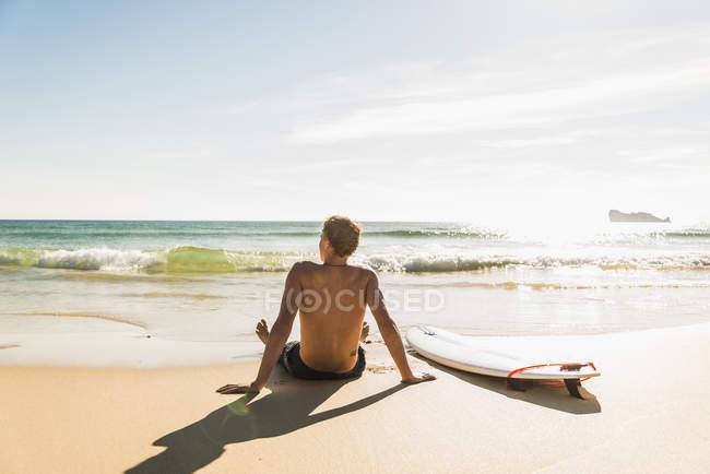 Adolescente sentado na prancha no mar — Fotografia de Stock