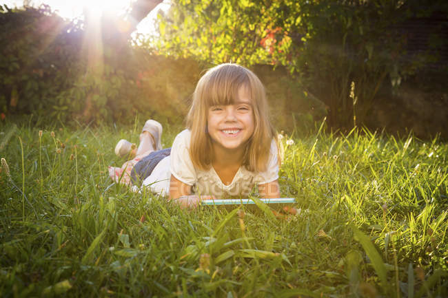 Portrait of grinning little girl lying on meadow with tablet — Stock Photo
