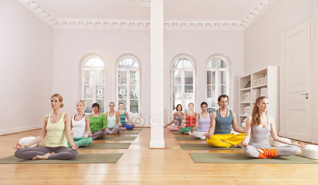 Group of people in yoga studio sitting in Lotus pose — Stock Photo