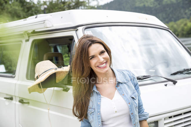 Woman standing beside van — Stock Photo