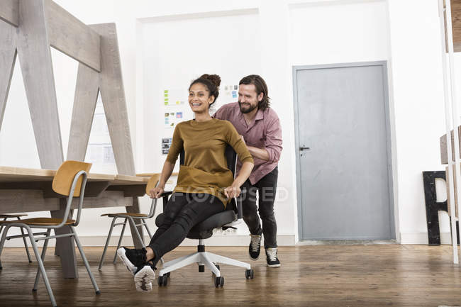 Man pushing happy woman on office chair — Stock Photo