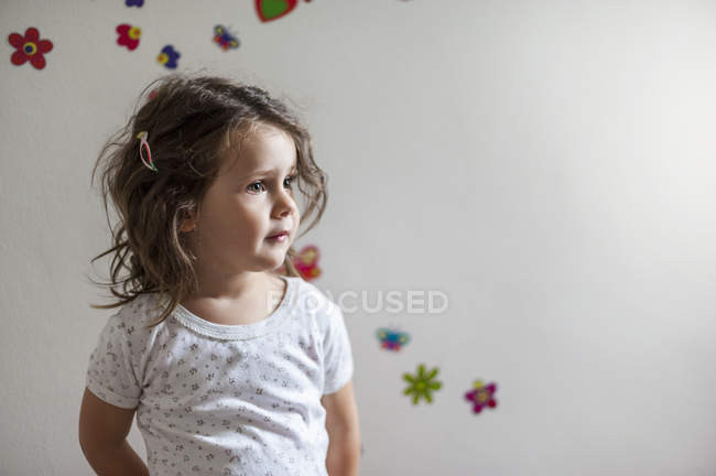 Girl standing in front of wall decorated with flowers — Stock Photo