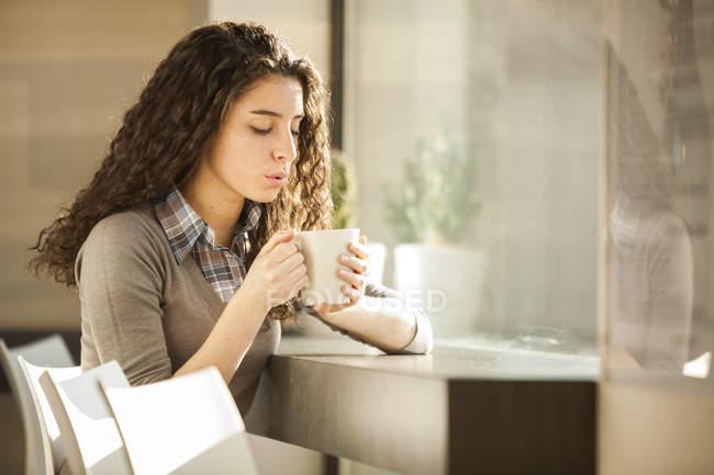 Молодая женщина с чашкой кофе в кафе — стоковое фото