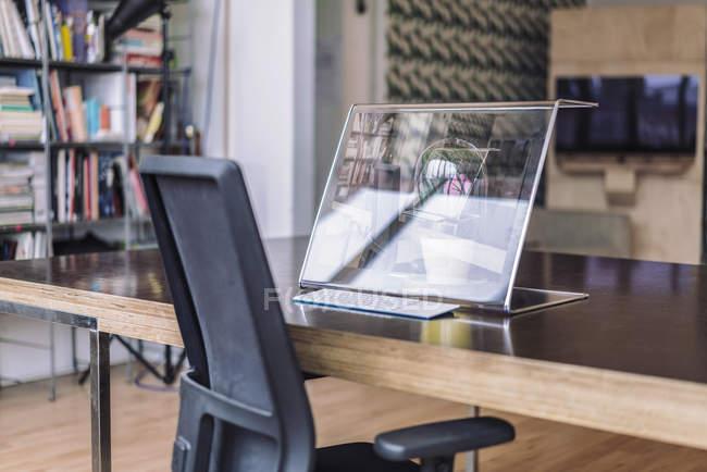 Futuristic computer on desk in creative office — Stock Photo