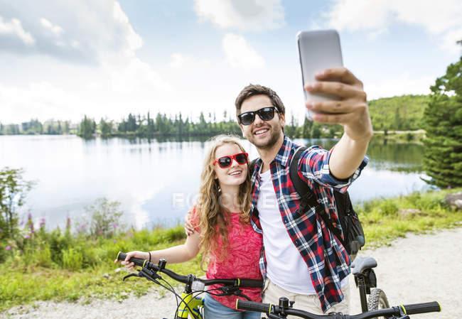Jovem casal tirando selfie em viagem de bicicleta — Fotografia de Stock