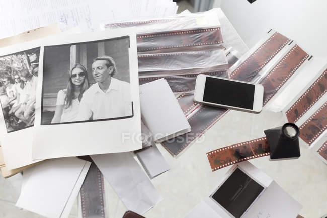 Photographies e strisce di pellicola sulla scrivania con smartphone — Foto stock