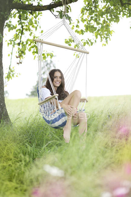Happy woman relaxing in a hanging chair — Stock Photo
