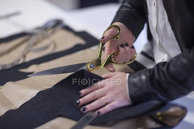 Close-up de corte de tecido costureira no showroom de moda — Fotografia de Stock