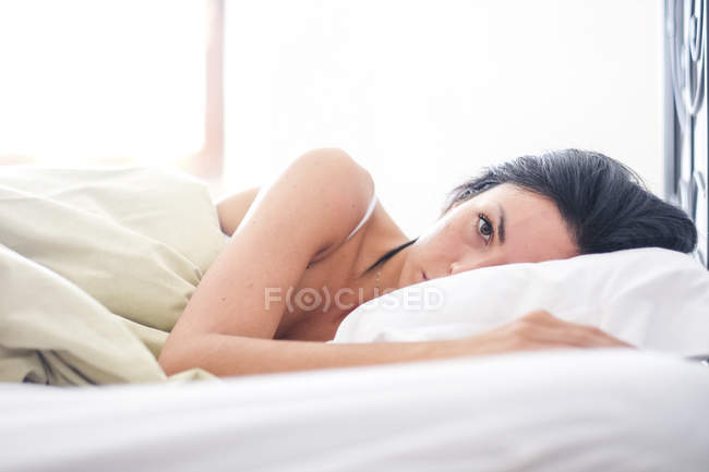 Woman lying on bed, waking up in the morning — Stock Photo