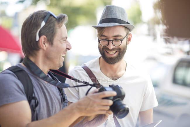 Двое мужчин счастливыми с камеры на открытом воздухе — стоковое фото