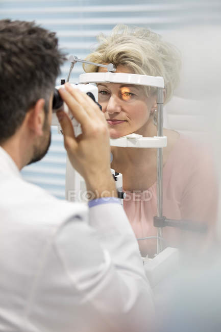 Eye doctor examining woman's vision — Stock Photo
