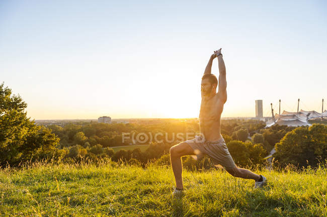 Shirtless athlete stretching on meadow at sunset — Stock Photo