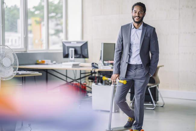 Homme d'affaires avec scooter debout dans le bureau — Photo de stock