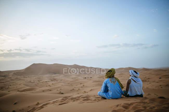 Donna che si siede nel deserto con guida berbera, guardando il tramonto — Foto stock