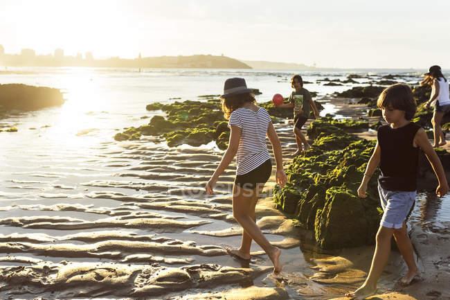Kinder spazieren im Sommer bei Sonnenuntergang am Strand — Stockfoto