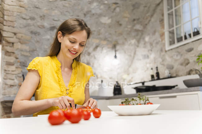 Smiling Woman cutting fresh tomatoes in kitchen — Stock Photo