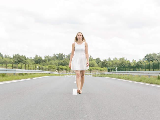 Молодая женщина в белом платье ходит босиком по проселочной дороге — стоковое фото