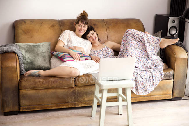 Two friends on leather couch  watching movie on laptop — Stock Photo