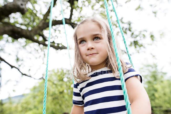 Retrato de niña en un columpio - foto de stock