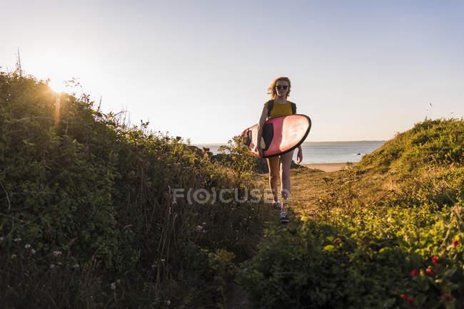 Teenage girl on the beach carrying surfboard — Stock Photo