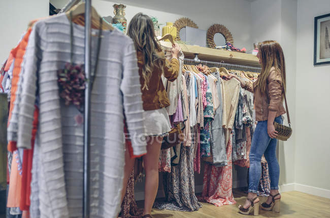 Two women shopping for clothes in a boutique — Stock Photo