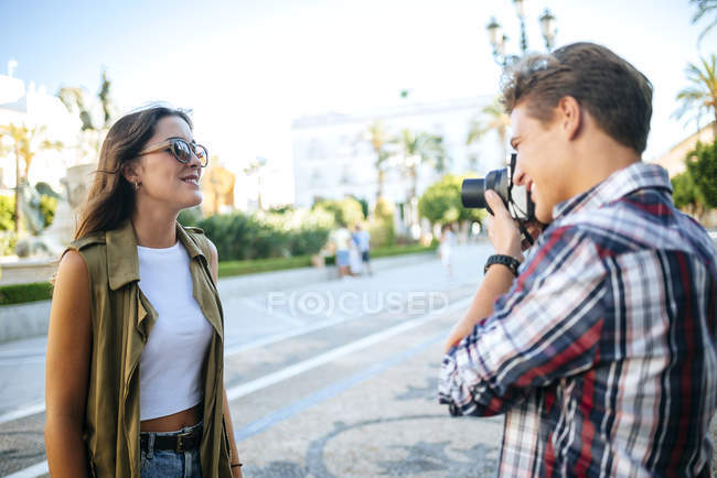 Young man taking picture of girlfriend — Stock Photo