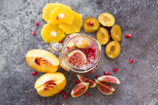 Jar of infused water with orange slices, fig, pomegranate seeds, nectarine and plums — Stock Photo