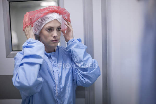 Woman putting on sterile protective clothing — Stock Photo