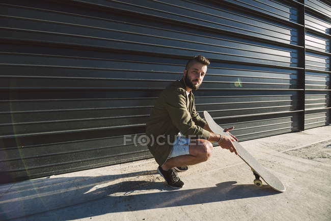 Man crouching with skateboard — Stock Photo