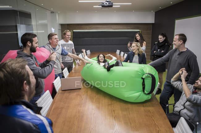 Grupo de pessoas de negócios brincando com sofá inflável — Fotografia de Stock