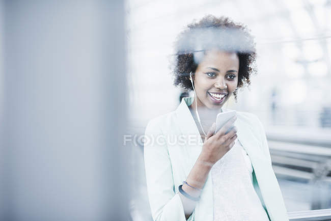 Woman with earphones and smartphone standing at platform — Stock Photo