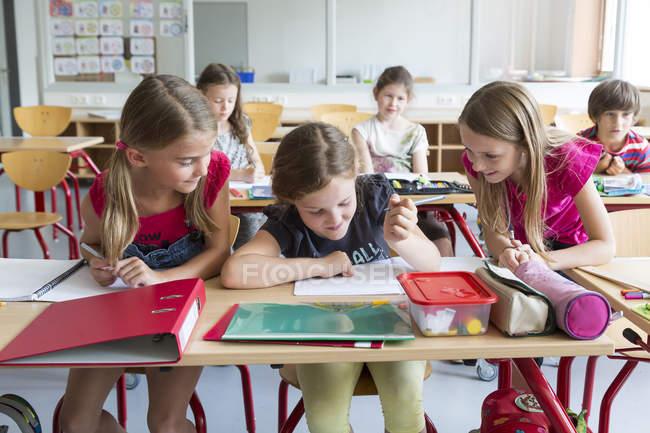 Scolare felici studiando in classe a scuola — Foto stock