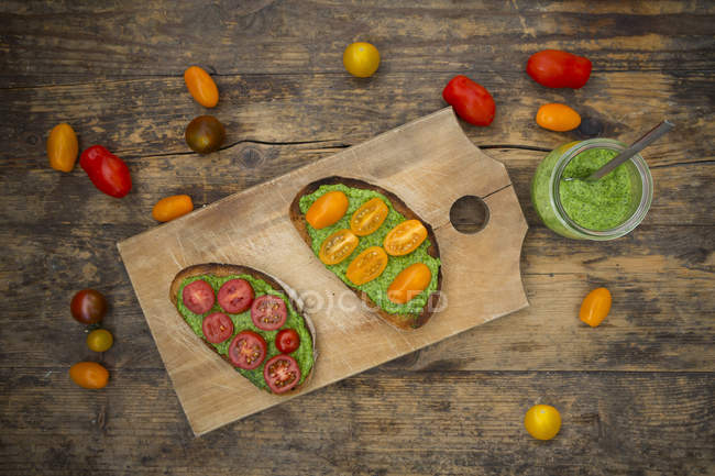Toasted bread slices with pesto and tomato on wooden board, top view — Stock Photo