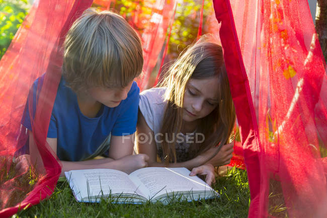 Sister and brother lying on a meadow under mosquito net reading a book together — Stock Photo