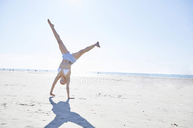 Young woman doing a cartwheel on the beach — Stock Photo