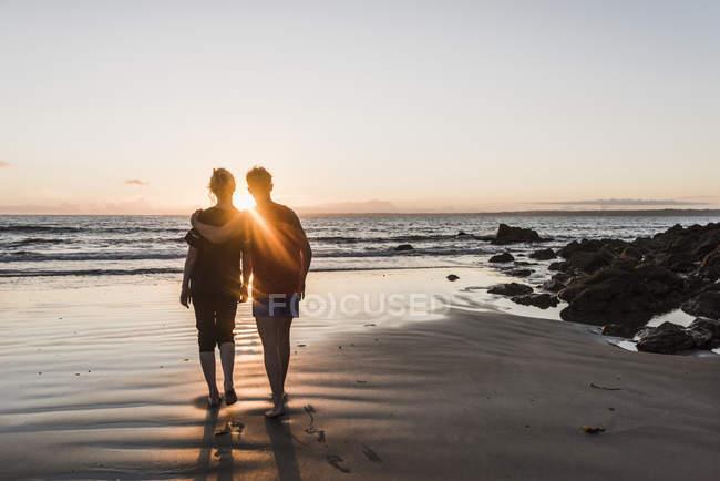 França, Península de Corzon, casal caminhando na praia ao pôr do sol — Fotografia de Stock